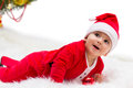 Christmas baby happy smiling lying on tummy wearing a red and white santa hat and suit isolated on a white background Royalty Free Stock Photography