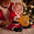Christmas baby and mom open gifts under the fir tree Stock Image