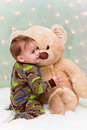 Christmas baby in pajamas holding teddy bear Stock Photos