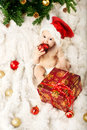 Christmas baby in red hat on fur and eatin Stock Photo