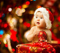 Christmas baby in santa hat near red present gift box holding ball Royalty Free Stock Images