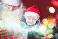 Christmas baby and Santa opening a present or gift box Royalty Free Stock Photo