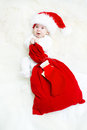 Christmas baby wearing red hat holding bag Stock Image
