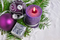 Christmas background with candle and decorations.Purple and silver Christmas balls over fir branches in the snow Royalty Free Stock Photo