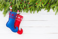 Christmas background. Christmas fir tree with decoration, red and blue Christmas socks on white wooden background, copy