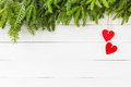 Christmas background. Christmas fir tree, red hearts decoration on white wooden background with copy space Royalty Free Stock Photo