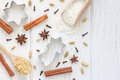 Christmas background with different spices, flour and cookie cutters on white wooden table, copy space, top view