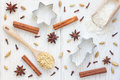 Christmas background with different spices, flour and cookie cutters on white wooden table, top view