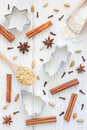 Christmas background with different spices, flour and cookie cutters on white wooden table, vertical