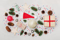 Christmas background of gift box, fir tree, conifer cone and holiday decorations on white desk top view. Flat lay styling. Royalty Free Stock Photo