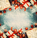 Christmas background with gift boxes red festive holiday decorations and paper snowflakes top view frame Stock Photos