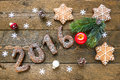 Christmas background with gingerbread numbers 2016, fir branches and decorations on the old wooden board. Royalty Free Stock Photo