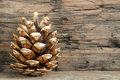 Christmas background with golden fir cone on wood Stock Photos