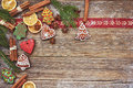 Christmas background. Homemade gingerbread cookies, cinnamon, Christmas tree on old wooden background. Toned, soft focus, copy spa
