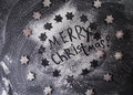 Christmas background. Merry Christmas written with flour and biscuits stars. Royalty Free Stock Photo