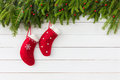 Christmas background. Red Christmas socks on white wooden background with Christmas fir tree. Copy space Royalty Free Stock Photo