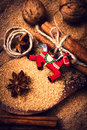 Christmas background with spices cinnamon sticks brown sugar anise star and red horse on wooden table close up still life festive Royalty Free Stock Photography