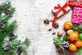 Christmas background with tangerines, nuts, spices and gift boxes Royalty Free Stock Photo