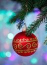 Christmas ball with ornament hanging on xmas tree, defocused lights