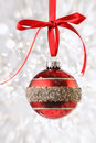 Christmas ball with ribbon on sparkly background Royalty Free Stock Image