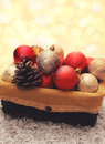 Christmas balls decorations with pine cone in box over garland Royalty Free Stock Photo