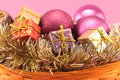 Christmas basket on pink background conceptual image about with boxes of gifts purples baubles and golden garlands Stock Images