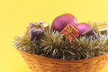 Christmas basket on yellow background conceptual image about with boxes of gifts purples baubles and golden garlands Royalty Free Stock Photography
