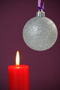 Christmas bauble and candle lit with copy space Royalty Free Stock Photos
