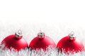 Christmas bauble postcard row of three red baubles in shiny white tinsel and copy space Stock Photography