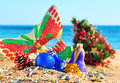 Christmas baubles, mask, christmas tree in beach Royalty Free Stock Photo