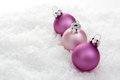 Christmas baubles pink balls on artificial snow with white background Royalty Free Stock Image