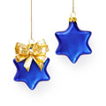Christmas baubles two blue stars decorated with gold bow hanging on ribbon Stock Image