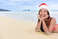 Christmas beach vacation cute girl in santa hat mixed race asian chinese portrait lying down relaxing posing on white sand a Royalty Free Stock Photography