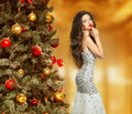 Christmas. Beautiful woman model in fashion dress. Makeup. Healthy long hair style. Elegant lady in red gown over xmas tree lights Royalty Free Stock Photo