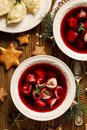 Christmas beetroot soup, borscht with small dumplings with mushroom filling in a ceramic bowl on a wooden table, top view. Royalty Free Stock Photo