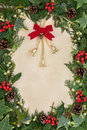Christmas bell decoration floral border with holly ivy and mistletoe on old parchment paper background Stock Photos