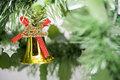 Christmas bell ornament hang on tree branch with green backgroun Royalty Free Stock Photo