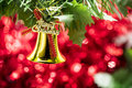 Christmas bell ornament hang on tree branch with red bokeh backg Royalty Free Stock Photo