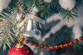 Christmas bell on snow covered branch Royalty Free Stock Photo