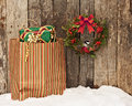 Christmas bird wreath with a little chickadee peeking out hanging on a rustic wooden wall beside a colorful bag filled with Stock Images