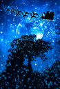 Christmas blue background. Silhouette of Santa Claus flying on a Royalty Free Stock Photo