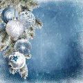 Christmas blue snowy background with beautiful balls, pine branches with frost and place for text or photo