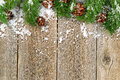 Christmas border decorations with snow on rustic wooden boards Royalty Free Stock Photo