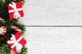 Christmas branches, gifts and candy canes border on white wood Royalty Free Stock Photo