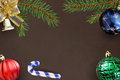 Christmas branches of spruce, stick, blue, green ribbed, red balloon and decorative bell on dark background Royalty Free Stock Photo