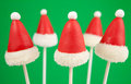 Christmas cake pops santa claus hat mini cakes on stick dipped in chocolate and decorated with fondant Royalty Free Stock Photo