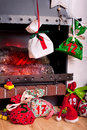 Christmas calendar bags as part of an advent hanging from a mantel or fireplace decorated for with fire glowing Royalty Free Stock Photography