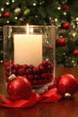 Christmas candle buring brightly in front of tree Royalty Free Stock Photo
