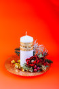 Christmas candle a decorative white over a warm orange background Royalty Free Stock Photos