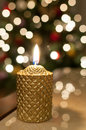 Christmas candle light burning and glittering tree lights in the background Stock Photo